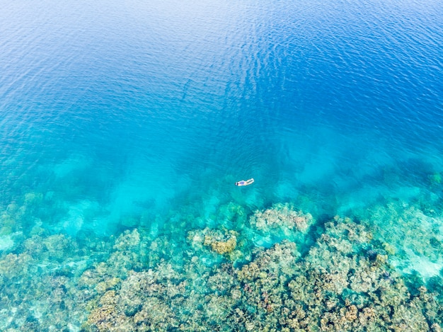 Aerial top down people snorkeling on coral reef tropical caribbean sea, turquoise blue water