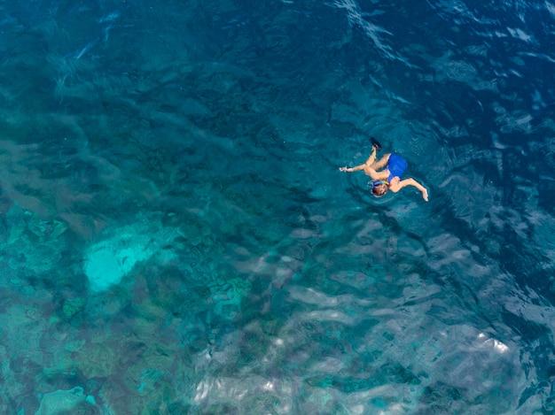 Aerial top down people snorkeling on coral reef tropical sea, turquoise blue water