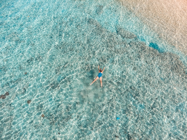 Воздушные сверху вниз люди подводное плавание на коралловом рифе тропического карибского моря, бирюзовой водой. индонезия архипелаг вакатоби, морской национальный парк, туристические места для дайвинга