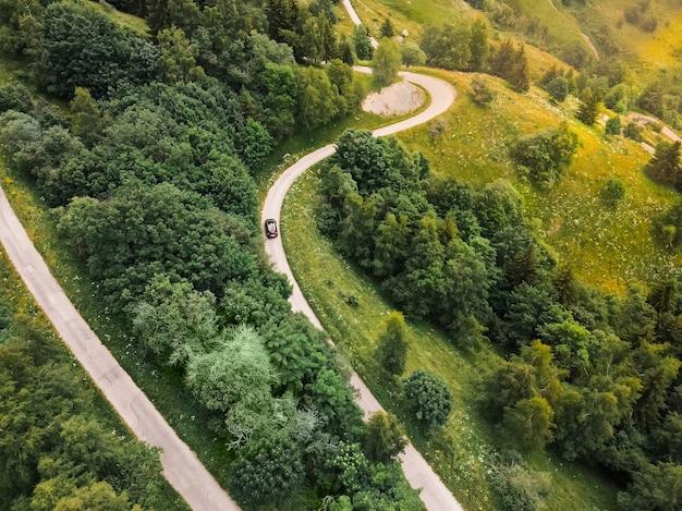 ヴォジャニー近くのフランスアルプスの山頂につながる美しいヘビの曲がりくねった道を運転している車の空中トップダウン写真。