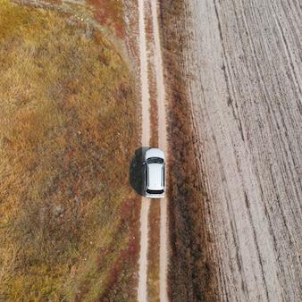 Aerial, top down view car driving down in rough terrain