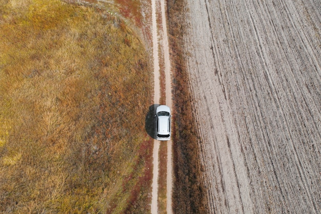 Aerial, top down view car driving down in rough terrain