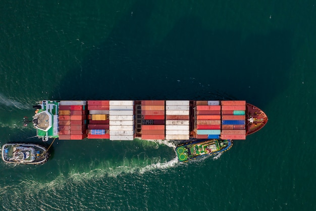 Aerial top down view over container freight cargo ship docking at sea port.