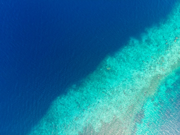 Aerial top down view coral reef tropical caribbean sea, turquoise blue water. indonesia moluccas archipelago, kei islands, banda sea. top travel destination, best diving snorkeling.