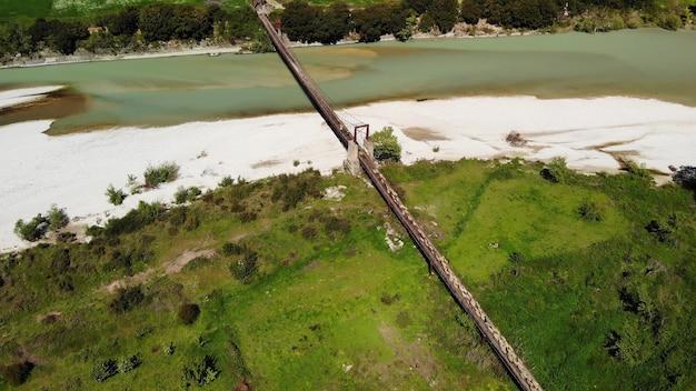 羊飼いと橋の上の山岳川を渡る羊と雄羊の空中トップダウンビュー