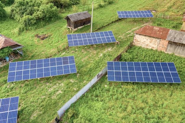 Воздушные сверху вниз панели солнечных батарей в зеленой сельской местности.