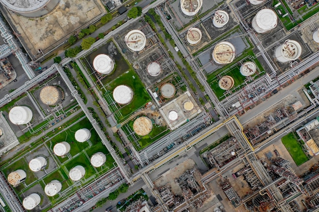Aerial top down view over oil refinery factory with many storage tanks and pipeline system.