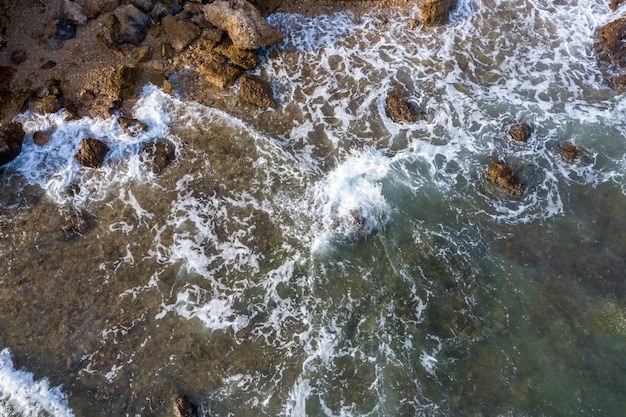 Aerial top down view over sea waves and rocky seacoast