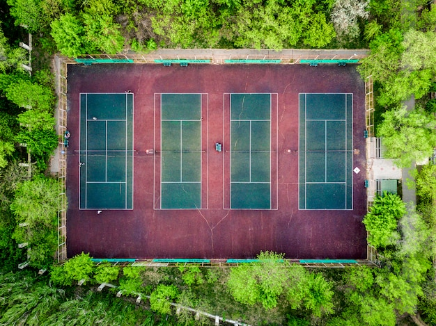 Aerial top down view of the tennis courts in the forest between trees