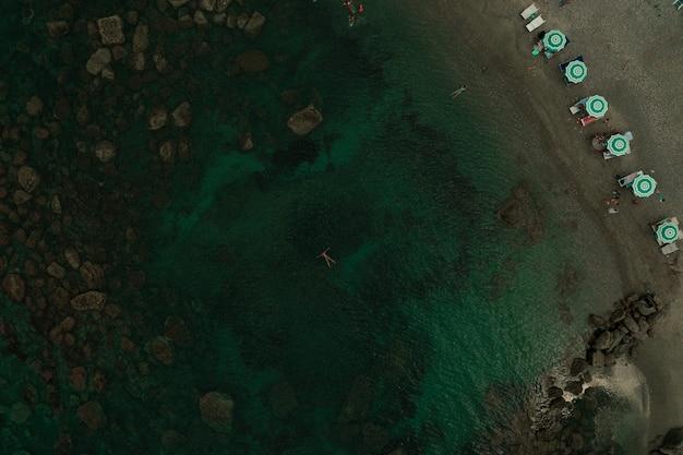 アルバニアの緑のターコイズブルーのアドリア海の上の空中トップネイチャービュー。水泳の美しい若い女性