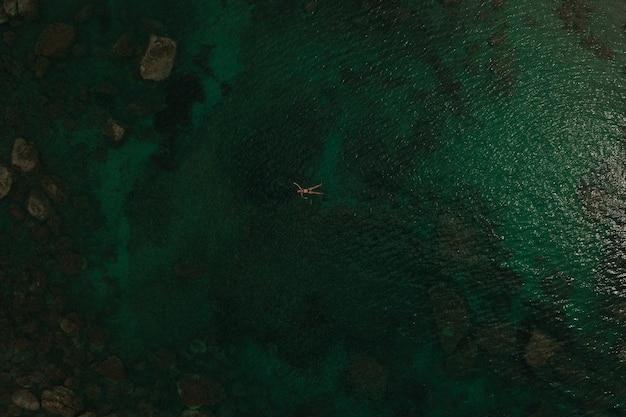 アルバニアの緑のターコイズブルーのアドリア海の上の空中トップネイチャービュー。美しい若い女性