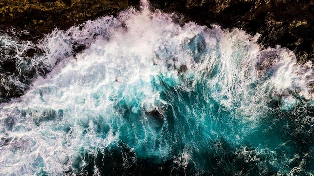 ビーチでの大きな波の空中上面垂直ビュー-海の力と危険な自然