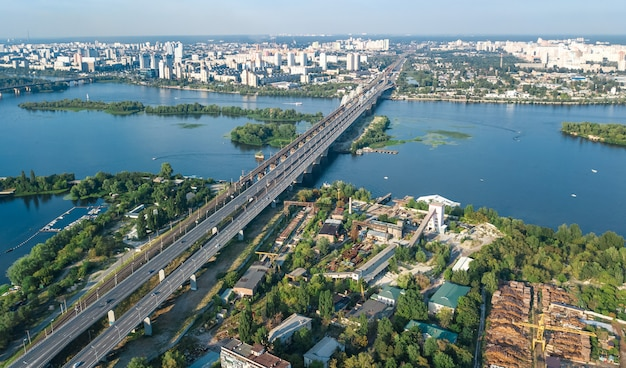 Aerial top view of automobile and railroad darnitsky bridge across dnieper river. city sunset skyline, ukraine
