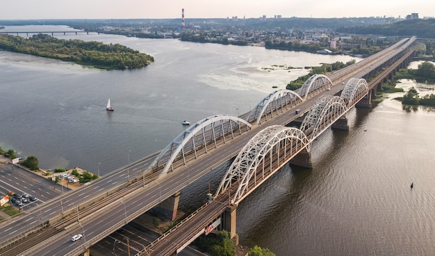 Aerial top view of automobile and railroad darnitsky bridge across dnieper river from above, kiev (kyiv) city sunset skyline, ukraine
