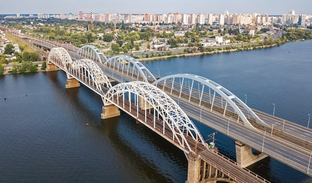 Aerial top view of automobile and railroad darnitsky bridge across dnieper river