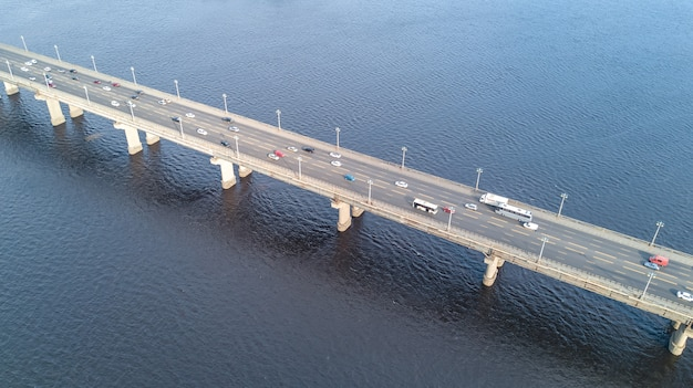 Aerial top view of bridge road automobile traffic of many cars from above