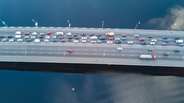 Aerial top view of the bridge with road automobile traffic of many cars