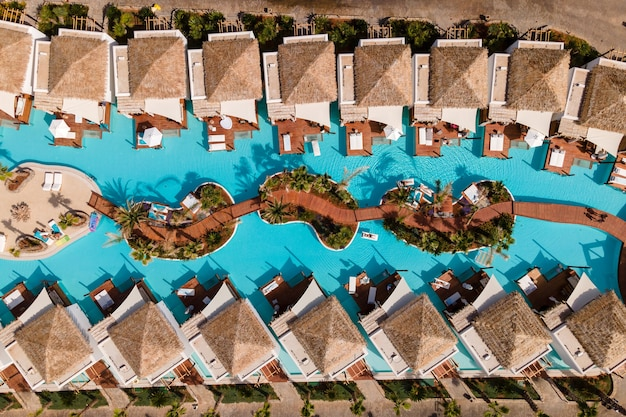 Дрон с высоты птичьего полета на тропический отель с бассейном.