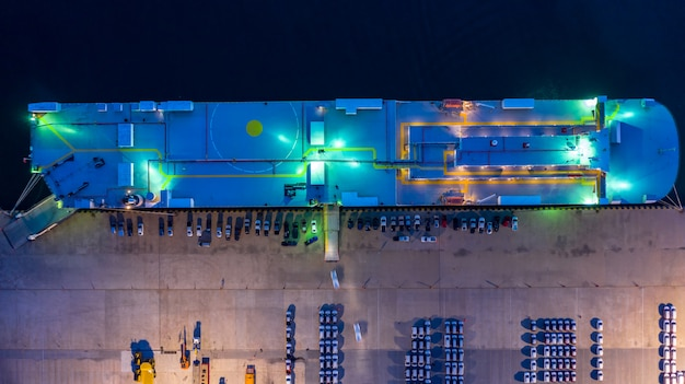 Aerial top view car carrier vessel at night