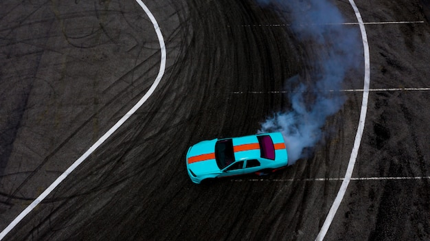 Aerial top view car drifting on asphalt race track with lots of smoke from burning tires.