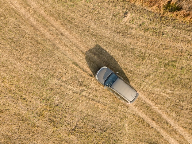 Aerial top view of car isolated on summer field texture background
