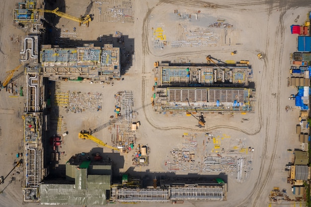Aerial top view construction site with industrial consgruction machinery building for new factory buildings.