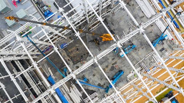 Aerial top view construction site with industrial machinery building for new  factory buildings.