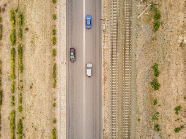 Aerial top view of countryside isolated road with railway tracks  f