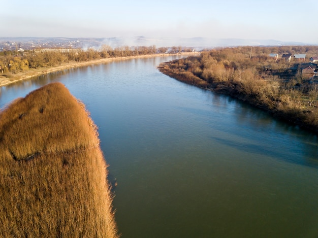 Aerial top view, countryside panorama of quiet river water and island with dry grass, misty horizon under blue sky on sunny day. drone photography.