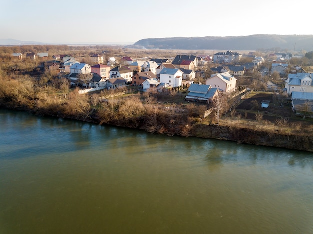 Aerial top view, countryside panorama of residential houses on river bank on blue sky and woody hill. drone photography.