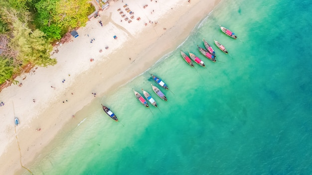 Aerial top view of crystal clear sea water and white beach with longtail boats from above, tropical island or krabi province in thailand