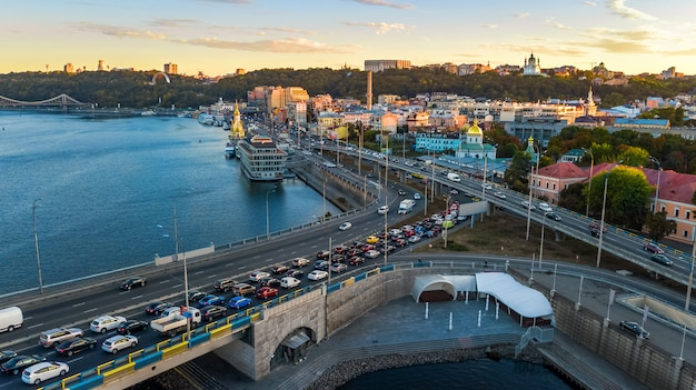 Aerial top view of dnieper river and podol district skyline from above, traffic jam on road, sunset in kiev (kyiv) city, ukraine