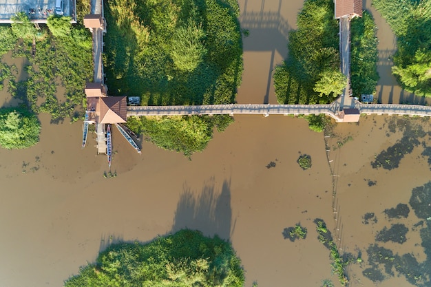 Aerial top view drone shot of bridge in the lake with longtail boats fisherman