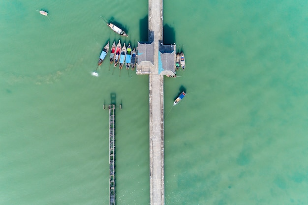 Aerial top view drone shot of bridge with long tail boats fisherman in summer season.