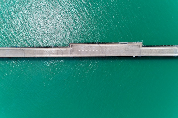 Aerial top view drone shot of small bridge in the sea image transportation.