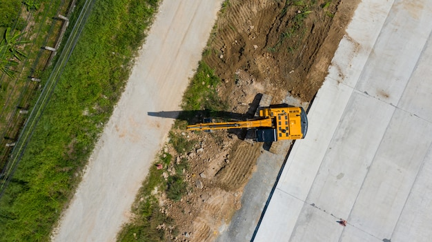 Aerial top view of excavator working in construction site