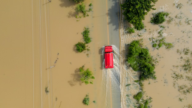 Aerial top view of flooded the village and country road with a red car