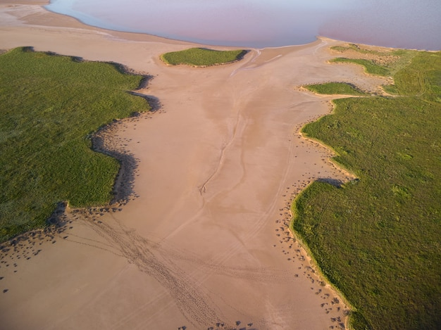 Aerial top view of green grass around a sandy ravine formed by rain