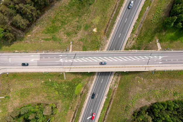 Aerial top view of highway multilevel junction, vehicles drive on roads, latvia