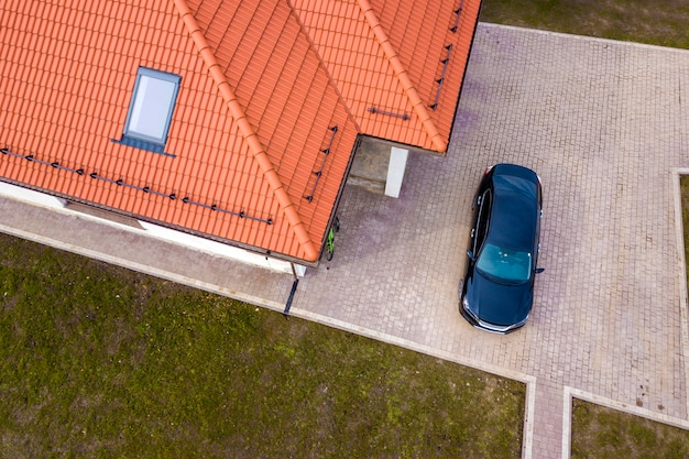 Aerial top view of house metal shingle roof with attic window and black car on paved yard.