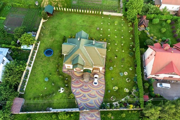 Aerial top view of house shingle roof and a car on paved yard.