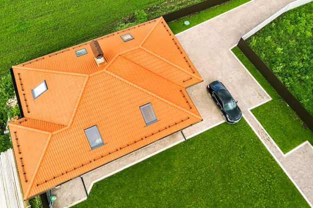 Aerial top view of house shingle roof with attic windows and black car on paved yard with green grass lawn.