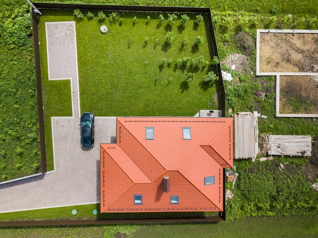 Aerial top view of house shingle roof with attic windows and black car on paved yard with green lawn.