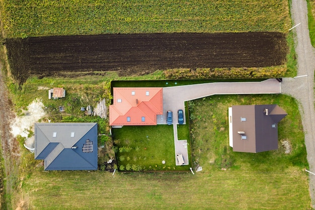 Aerial top view of house shingle roof with attic windows and cars on paved yard with green grass lawn.