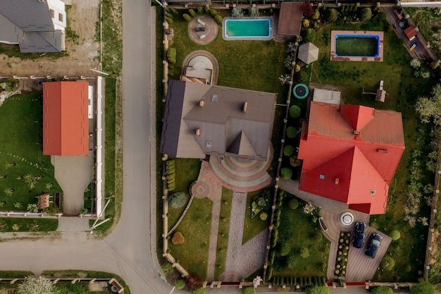Aerial top view of a house with paved yard with green grass lawn with concrete foundation floor.