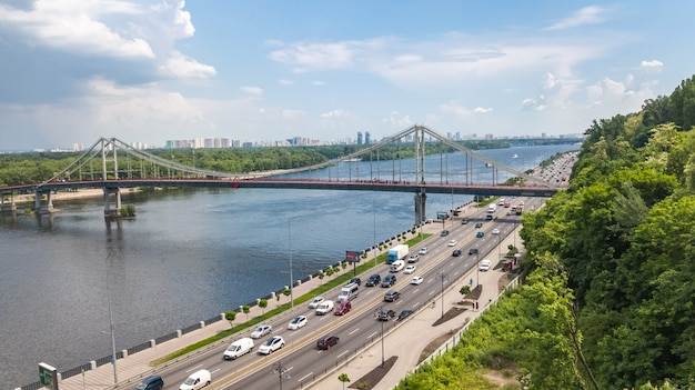 Aerial top view of kiev city from above, kyiv skyline, hills, pedestrian park bridge and dnieper river cityscape in spring, ukraine