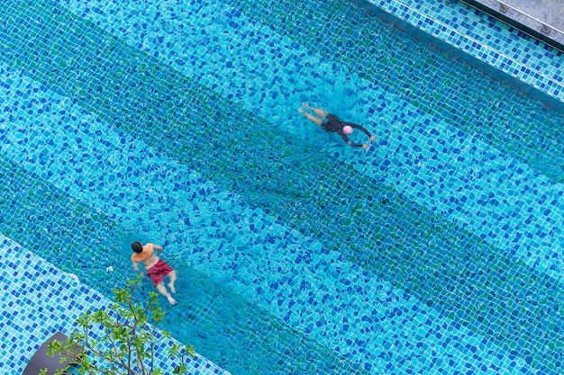 Aerial top view of man and boy swimming in the pool, playing in water