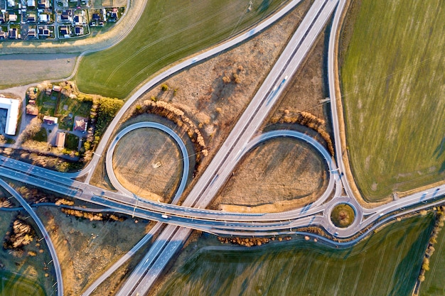 Aerial top view of modern highway road intersection, house roofs on spring green field. drone photography.