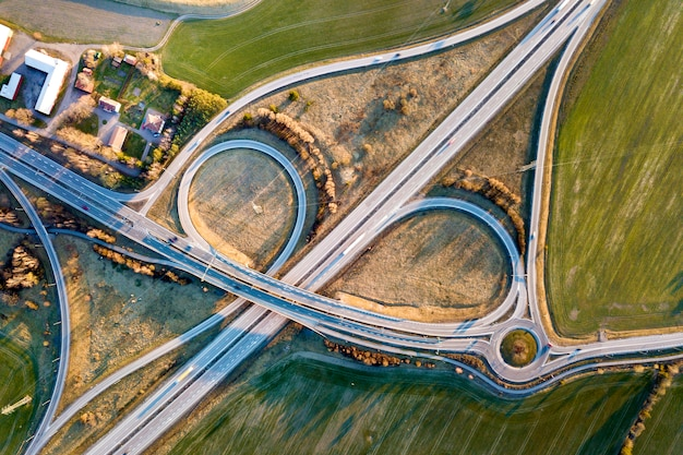 Aerial top view of modern highway road intersection, house roofs on spring green field