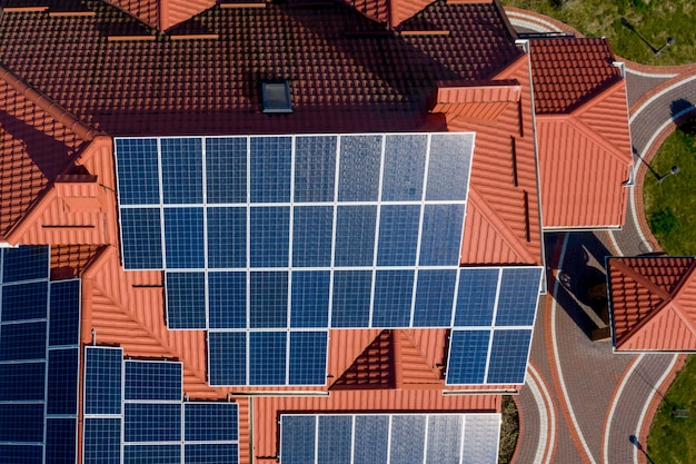 Aerial top view of new modern residential house cottage with blue panels. renewable ecological green energy production concept